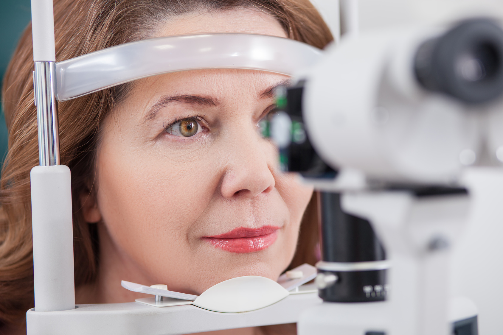 Pretty woman is looking into eye test machine with concentration in oculist lab. Focus on her face